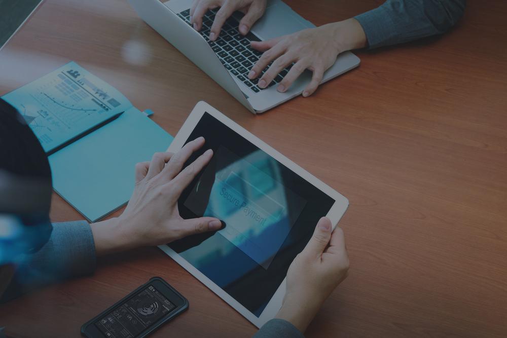 vista superior de dois colegas trabalhando com tablet e notebook