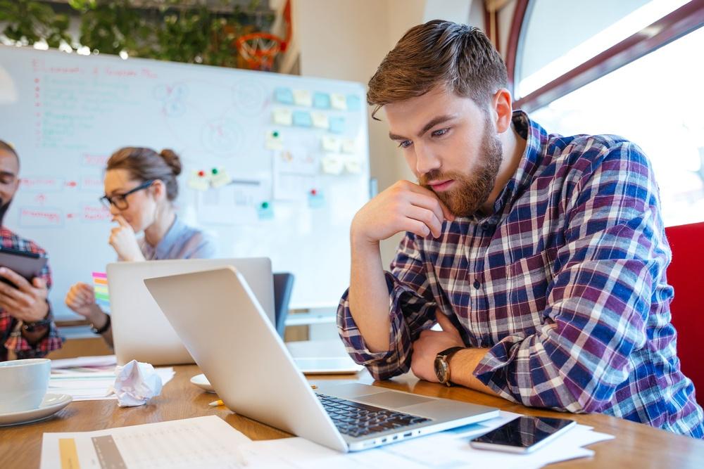 Jovem concentrado usando notebook enquanto seus colegas estudam juntos
