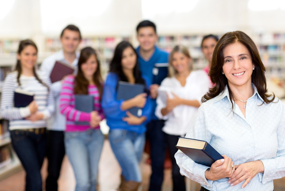 Female teacher smiling with a group of university students.jpeg