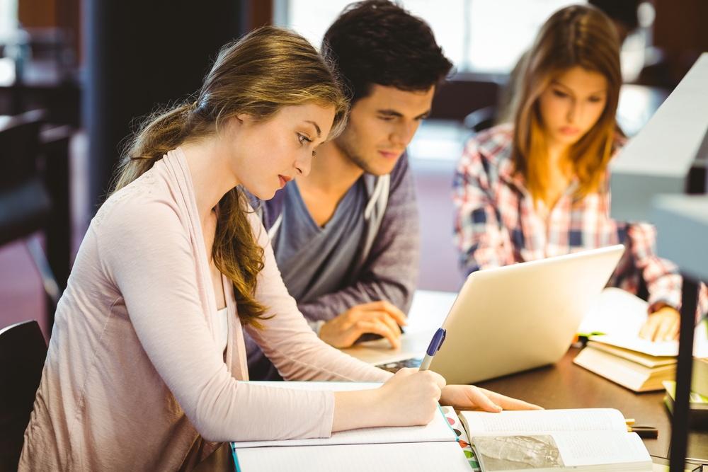 Colegas concentrados estudando com livros e um computador