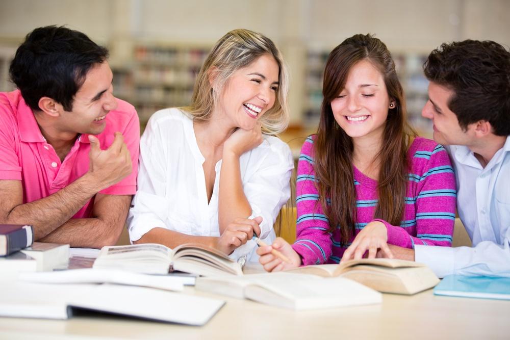 Amigos sorridentes estudando na biblioteca