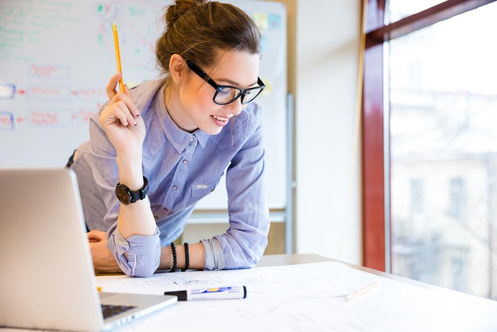 feliz mulher jovem analisando uma planta no escritório