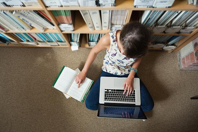 High angle view of a female student sitting against bookshelf with laptop on the library floor.jpeg