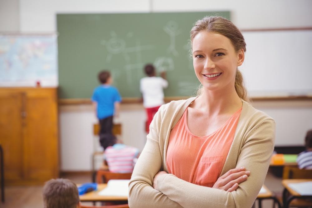 Professora na sala de aula sorrindo para a câmera e os alunos atrás escrevendo no quadro