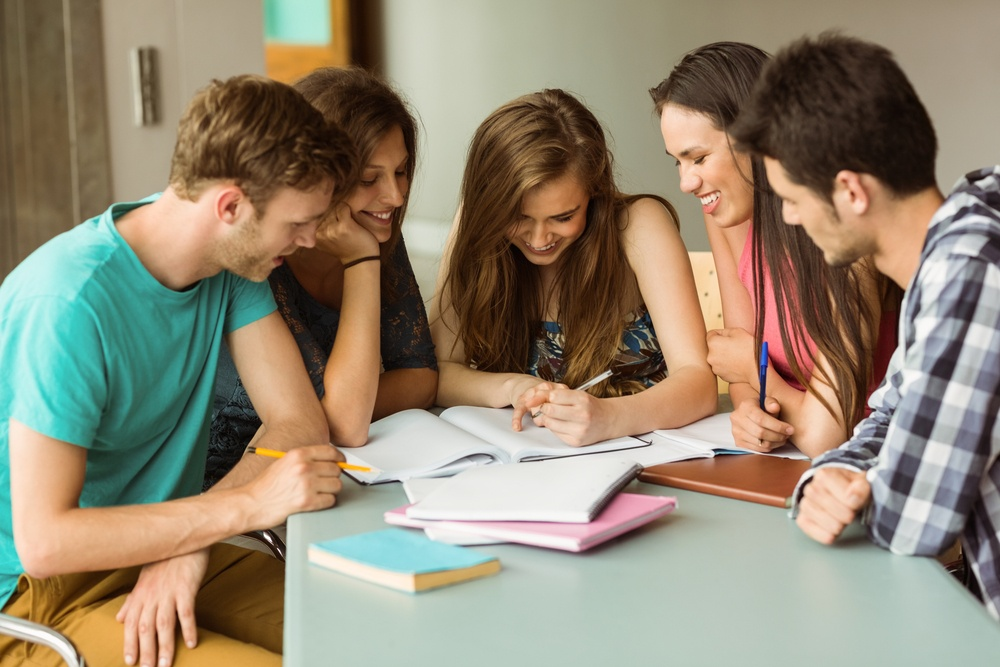 Smiling friends sitting studying together after school.jpeg