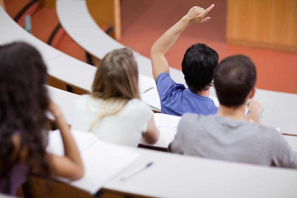 Jovem estudante levantando a mão para perguntar enquanto seus colegas tomam nota sobre a aula