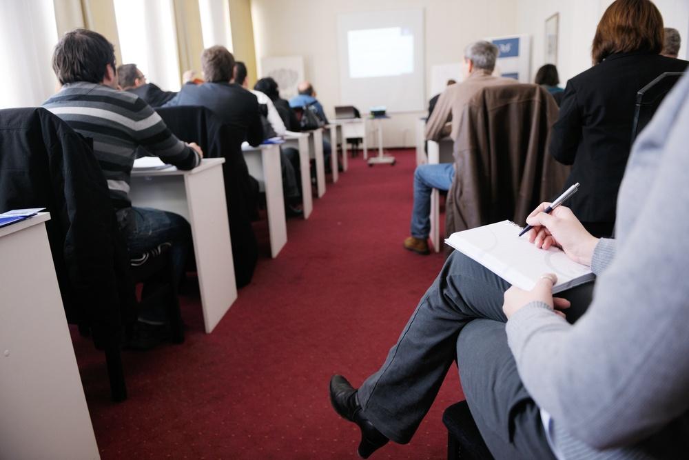 Grupo de pessoas tendo aula em pequena sala de conferência