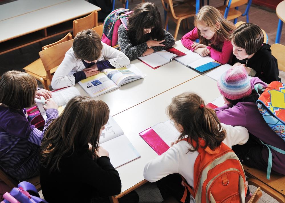 Crianças lendo em volta de uma mesa