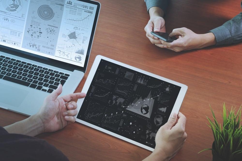 Vista superior de dois colegas discutindo dados com tablet e notebook