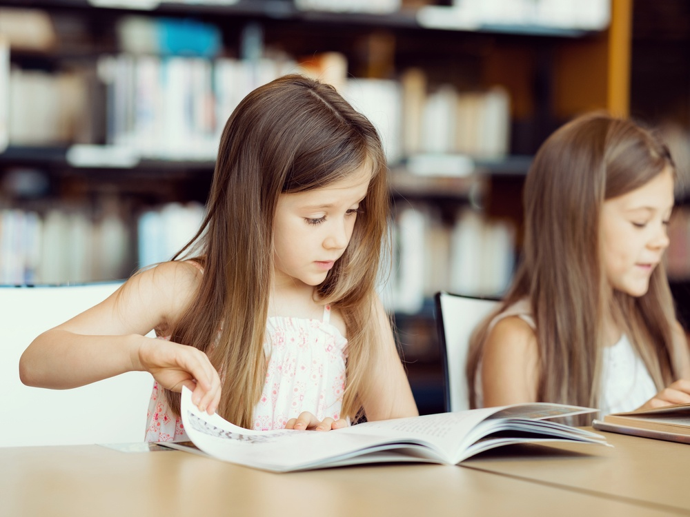 Little girls reading books in library.jpeg